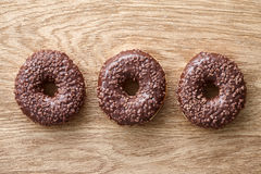 Three chocolate donuts on wooden rustic table Stock Image