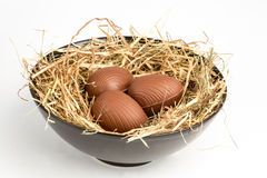 Chocolate easter eggs in straw in bowl Stock Photo