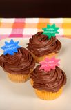 Three chocolate frosted cupcakes with Royalty Free Stock Photography