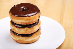 Three chocolate glazed donuts Stock Photo