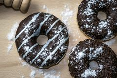 Three chocolate glazed donuts. With powdered sugar, on a wooden board. Ideal for breakfast Stock Photography