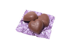 Three chocolate heart candy in puple foil on white background.  Stock Photos