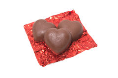 Three chocolate heart candy in red foil on white background Stock Photography