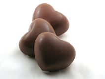 Three chocolate hearts. Three chocolate heart candies on white Stock Images