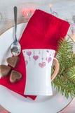 Beautiful mug and three chocolates shaped heart on red napkin an royalty free stock photos