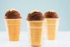 Three chocolate ice cream scoops with vanilla sauce Royalty Free Stock Photos