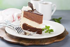 Three chocolate layer mousse cake. Slice on a plate Stock Image
