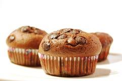 Three chocolate muffins. Three isolated chocolate muffins with raisins Royalty Free Stock Image