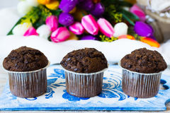 Three chocolate muffins on a background of tulips. Chocolate muffins on the board written under gzhel Stock Photo