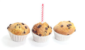 Three chocolate muffins with a candle. Isolated on white background stock photos