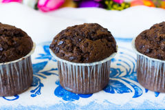Three chocolate muffins with chocolate chips. Chocolate muffins on the board written under gzhel Royalty Free Stock Photography