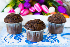 Three chocolate muffins on a flowers background. Chocolate muffins on the board written under gzhel Royalty Free Stock Photo