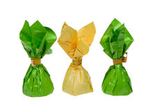 Three chocolate truffles. Candies in green and yellow foil isolated on white background Royalty Free Stock Image