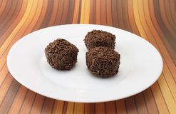 Three chocolate truffles on a white plate Royalty Free Stock Image