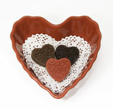Three Chocolate Valentines in Heart Shaped Bowl. Homemade light, dark, and red chocolate hearts on a white lace doily in a red heart shaped bowl against a white royalty free stock image