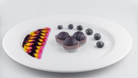 Three chocolates balls in decorative plate with blackberry royalty free stock photo