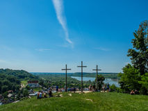 Three christian crosses on the hill with people en Royalty Free Stock Image
