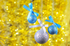 Three christmas ball on golden bokeh background, space for your Stock Images