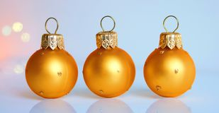 Three christmas balls. On the blue background royalty free stock photography