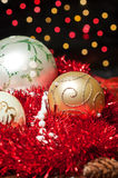 Three christmas balls. Over tinsel waiting to be put on a tree Stock Photography