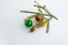 Three Christmas balls, fir branch and fir cones on a white backg Stock Photography