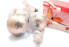 Three christmas balls with silver ribbon and gifts Royalty Free Stock Photo