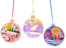 Three christmas balls with winter landscape on the. Three attractive Christmas balls with winter landscape on them hanging on tinsel over white Royalty Free Stock Image