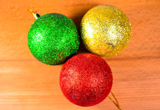Three Christmas balls on wooden table Royalty Free Stock Photography