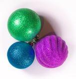 Three christmas baubles blue, green, purple Royalty Free Stock Photo