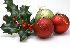 Three Christmas baubles with holly. Three shiny red and gold Christmas tree decorations with a sprig of holly Stock Image