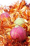 Three Christmas baubles with orange tinsel. Three pink and yellow Christmas baubles with orange tinsel on white background Stock Photography