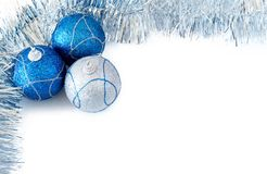 Three Christmas baubles with silver tinsel. Three blue and silver Christmas baubles with silver tinsel forming a frame on white backgound Stock Photo