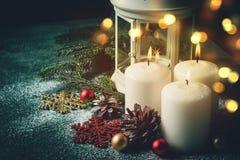 Three Christmas burning candles and lantern on dark turquoise background Royalty Free Stock Photos