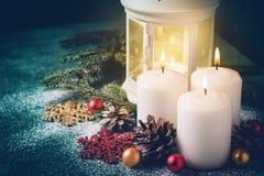 Three Christmas burning candles and lantern on dark turquoise background Royalty Free Stock Images