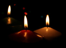 Three Christmas Candles. Up close, with festive lights in the background Stock Photo