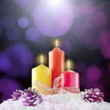 Three christmas candles in a bokeh background Stock Photos