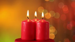 Three christmas candles burning on blurry xmas lights background stock video