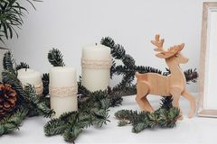 Three Christmas candles, pinecone, baubles, branch of pine, gsarland and wooden deer on the white table. Celebration and royalty free stock images