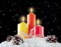 Three christmas candles in a snow background Stock Images