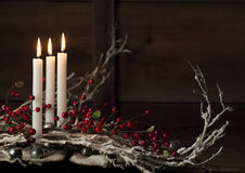 Three Christmas Candles. Three white candles, all with flames, surrounded with snow covered branches and red berry branches Stock Images