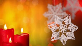 Three christmas candles and xmas decorations hanging against blurry lights background stock video