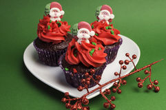 Three Christmas Cupcakes against a green background. Stock Photos