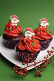 Three Christmas Cupcakes against a green background - vertical Stock Images
