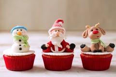 Three christmas cupcakes. Santa claus snowman and reindeer Stock Photos