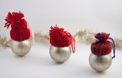Three Christmas decoration balls with handmade red hats. Christmas decoration balls wihh red hats. Silver ribbon, soft white background Royalty Free Stock Images
