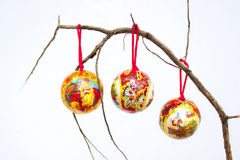 Three Christmas Decorations On A Dry Branch Royalty Free Stock Image