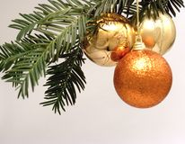 Three Christmas decorations hanging from a tree. Three gold and bronze Christmas decorative balls hanging from a Christmas tree Royalty Free Stock Image