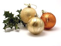 Three Christmas decorations and holly. Three Christmas decorations, gold and bronze balls with a sprig of holly Stock Photos