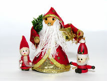 Three Christmas dolls. Christmas dolls decorated like Santa Claus and red elves on a white background Stock Image