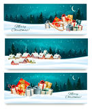 Three Christmas festive banners with landscapes and gift boxes. Royalty Free Stock Image